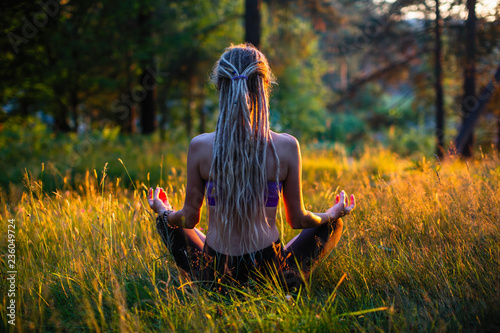 Yoga woman silhouette in Lotus pose on a picturesque glade in a green forest. - 236049724