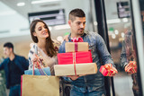 Young couple doing Christmas shopping in the shopping mall - 236060987