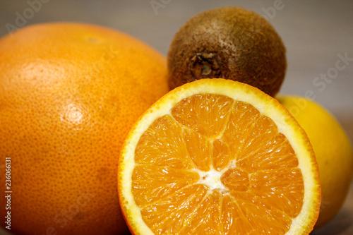 Różnorodna surowa cytrus owoc na drewnianym stole. Close-up z cytryny, pomarańczy, grejpfruta i kiwi.