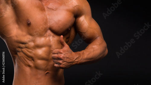 Silna Sportowa mężczyzna sprawności fizycznej modela półpostać pokazuje sześć paczek abs na ciemnym tle.