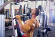 male bodybuilder doing exercises in a gym