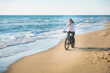 Beautiful young woman rides a Bicycle along the sea on a sandy beach.
