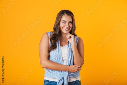 Leinwandbild Motiv Portrait of a cheerful young casual woman standing