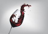 agiter un verre de vin rouge pour faire des éclaboussures sur un fond gris  - 236098562