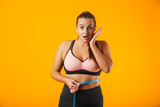 Portrait of excited chubby woman in sportive bra measuring her waist with meter, isolated over yellow background