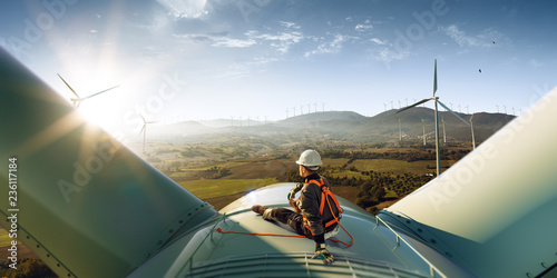 Leinwanddruck Bild Happy engineer feel success after good work. He standing a top of windmill and looking beautiful sunset landscape