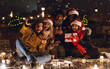 Leinwanddruck Bild - Happy young group of friends sitting outdoors in evening in christmas hats drinking coffee.