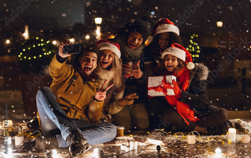 Happy young group of friends sitting outdoors in evening in christmas hats drinking coffee. - 236118141