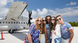 Leinwandbild Motiv travel, tourism and people concept - group of smiling friends or tourists taking picture by selfie stick over plane on airfield background