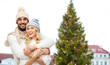 winter and holidays concept - happy couple in hats hugging over christmas tree at tallinn old town hall square background