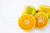 Half of green tangerine orange fruit on white table