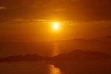 Sunset over the sea. Bright colorful background with sun, sea and rocks © sergeimalkov13