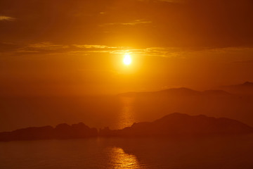 Sunset over the sea. Bright colorful background with sun, sea and rocks