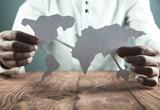 Businessman showing paper world map. Business concept