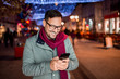 Portrait of a young man using smartphone on the street with Christmas decoration.