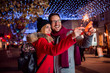 Couple with sparklers enjoying Christmas party in the city street. - 236142985