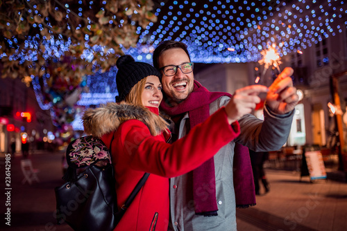 Plakat Couple with sparklers enjoying Christmas party in the city street.