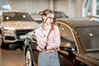 Young beautiful woman hesitates choosing a new car in the showroom