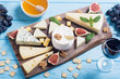 Leinwanddruck Bild - Cheeseboard with cheese brie , parmesan , camembert and dorblu . Food on wooden board