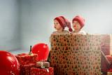 Portrait of adroable twin-elves among huge Christmas presents - 236186504
