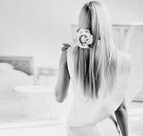 Black&white portrait of a lady holding a rose flower in hotel's room - 236186542