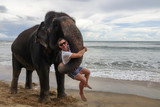 Portrait of a young guy with an elephant on the background of a tropical ocean beach. Elephant hugs a young man with his trunk. Tropical coast of Sri Lanka.