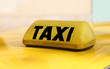 writting taxi in black on a yellow taxi