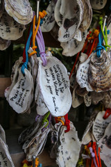 Foreign wishes. Writen wishes on oyster shells (Ema) at Kakigara Inari a Shinto Shrine at the Hase-dera temple in Kamakura, Kanagawa Prefecture, Japan. © marksteel