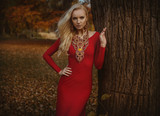 Pretty blond woman posing in an autumnal park - 236196353