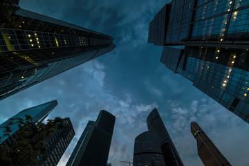 bottom-up view of skyscrapers and flying clouds