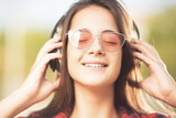 Beautiful happy teenage girl with her eyes closed  listening to music