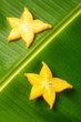 Slices of ripe yellow star fruit carambola or star apple ( starfruit ) on green banana leaf, vertical composition