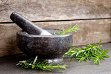 Fresh sprigs of Rosemary herb leaves with marble mortar and pestle against wooden background - side view - 236221757