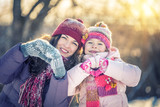 Little girl and her mother playing outdoors at sunny winter day - 236231930