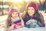 Little girl and her mother playing outdoors at sunny winter day - 236232113