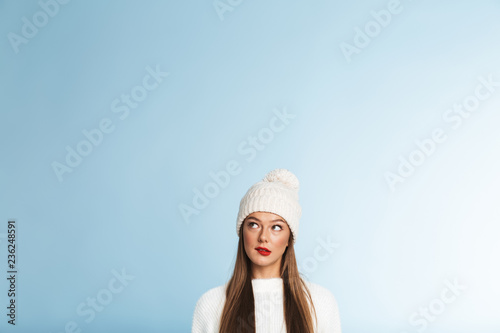 Thinking young woman wearing winter hat posing isolated over blue wall background. - 236248591