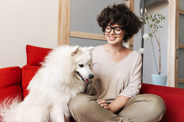 Curly woman sitting on sofa with her cutie white dog.