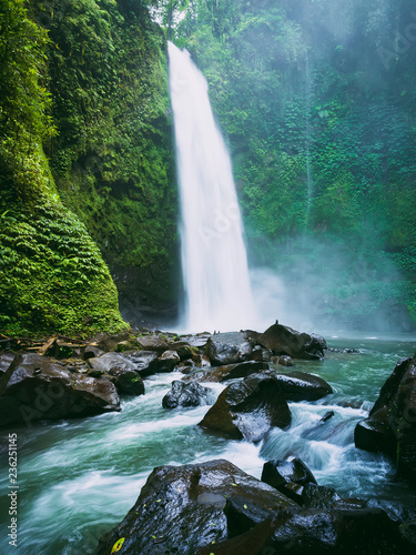 Leinwanddruck Bild Powerful waterfall with river in Bali. Tropical forest and waterfall