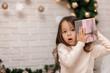 Leinwandbild Motiv Pretty smiling girl holding Christmas gift in hand