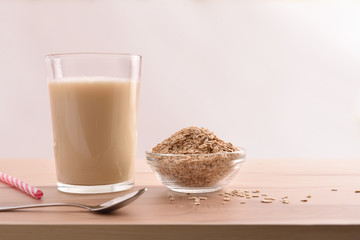 Oat drink in glass and cereal flakes white background