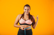 Portrait of pretty chubby woman in sportive bra measuring her waist with meter, isolated over yellow background