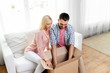 Leinwandbild Motiv delivery, mail and people concept - happy couple with open parcel box at home