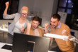 business, success and teamwork concept - happy coworkers with computer celebrating victory at night office