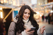 Close up of young smiling beautiful Caucasian woman using smart phone on the street on cold weather. - 236274181