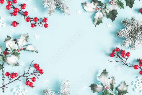 Christmas or winter composition. Frame made of snowflakes, fir tree branches and red berries on pastel blue background. Christmas, winter, new year concept. Flat lay, top view, copy space - 236277796