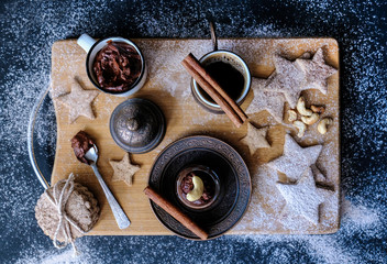 A beautiful Christmas still life of hot black coffee, homemade stars-shaped cookies, cinnamon sticks, flour and sugar sprinkles