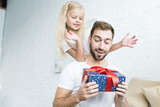 happy little daughter looking at surprised father holding gift box at home