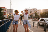 Two beautiful girls dancing on the bridge in the city. Going on the music festival.