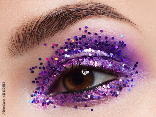 Beautiful macro shot of female eye with ceremonial makeup. Perfect shape of eyebrows, eyeliner and pretty blue gletter on eyelid. Cosmetics and make-up. Closeup macro shot of fashion sparcle visage - 236306183