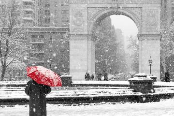 Person walking alone with red umbrella in black and white winter scene in Washington Square Park, New York City